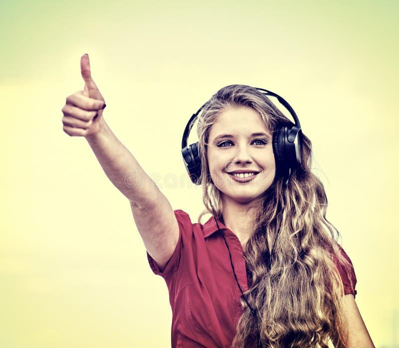 Το κορίτσι σπουδαστών στο ακουστικό ακούει μουσική παρουσιάζει αντίχειρα στοκ φωτογραφία με δικαίωμα ελεύθερης χρήσης
