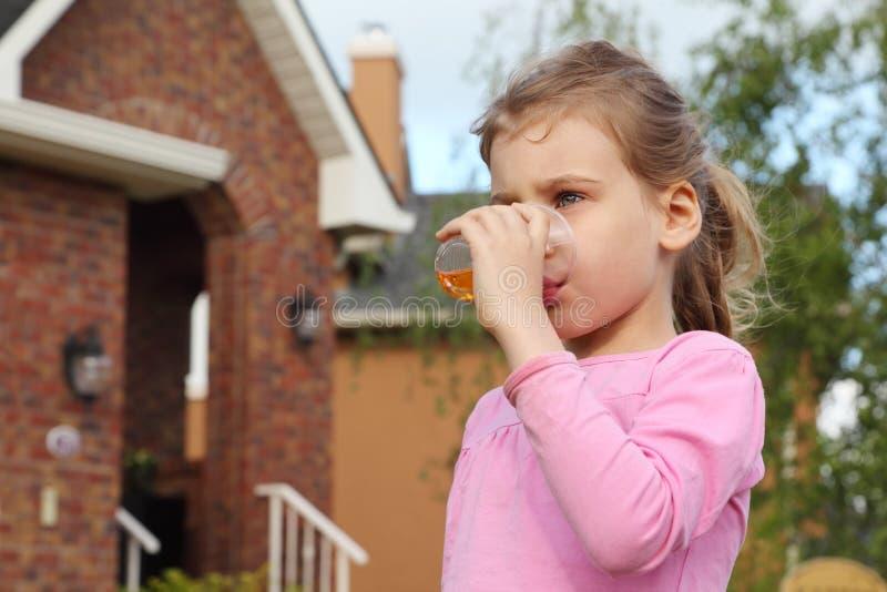 Το κορίτσι στέκεται κοντά στο εξοχικό σπίτι και πίνει το χυμό στοκ φωτογραφίες με δικαίωμα ελεύθερης χρήσης