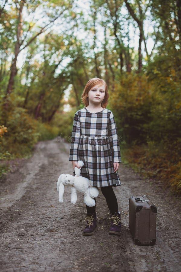 Το κορίτσι στέκεται στο δρόμο κρατώντας έναν λαγό βελούδου στοκ εικόνες