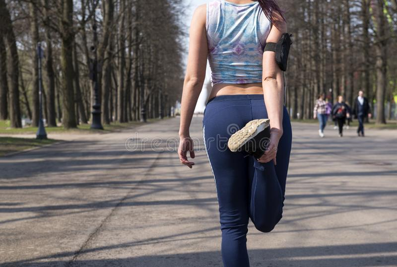 Το κορίτσι στα αθλητικά ενδύματα που κάνουν την προθέρμανση στο πάρκο, το κορίτσι συμμετέχει στον υπαίθριο αθλητισμό την άνοιξη στοκ φωτογραφίες με δικαίωμα ελεύθερης χρήσης