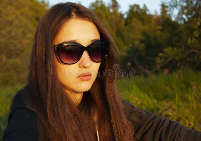 Το κορίτσι στα γυαλιά κάθεται στη μέση του δάσους και basks στον ήλιο στοκ φωτογραφίες