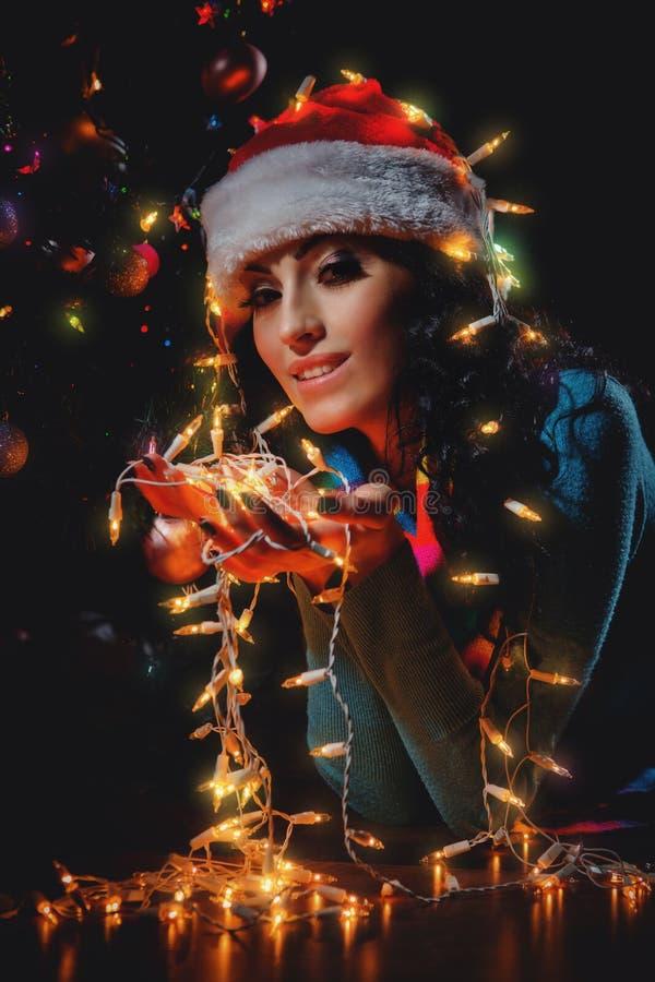 Το κορίτσι στα καπέλα Santa έχει Χριστούγεννα στοκ φωτογραφία