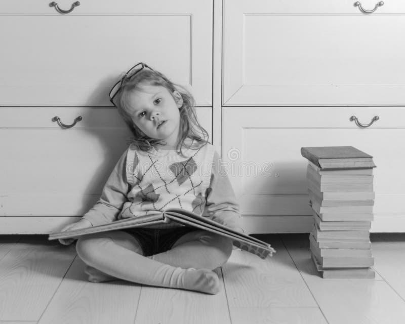 Το κορίτσι στα σημεία με τη συνεδρίαση βιβλίων στο πάτωμα, γραπτό στοκ εικόνες