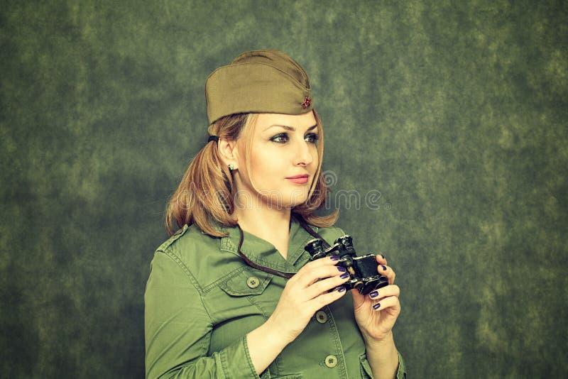 Το κορίτσι στα στρατιωτικά ενδύματα, στην ΚΑΠ του, με τις διόπτρες στοκ εικόνα με δικαίωμα ελεύθερης χρήσης
