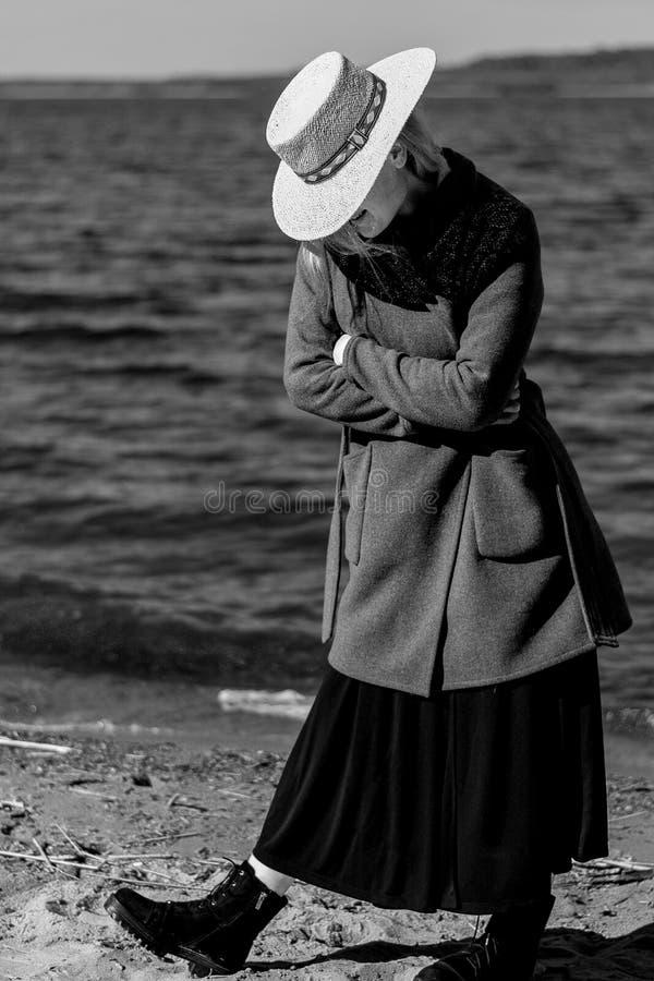 Το κορίτσι στην ακτή της δεξαμενής σε ένα καπέλο αχύρου και ένα παλτό Γραπτή φωτογραφία στοκ εικόνες με δικαίωμα ελεύθερης χρήσης