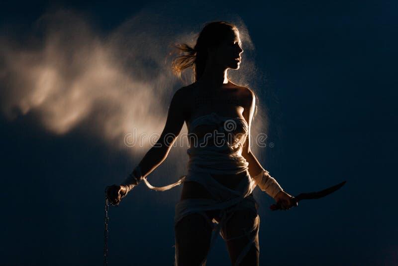 Το κορίτσι στην εικόνα της αιγυπτιακής μούμιας στέκεται με την αλυσίδα και το μαχαίρι μετάλλων στα χέρια της στοκ εικόνες