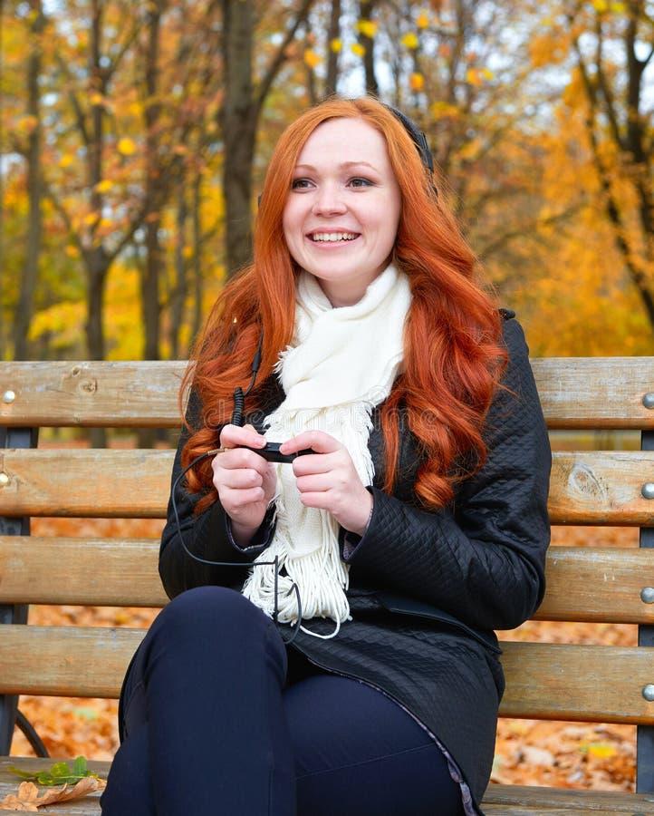 Το κορίτσι στην εποχή φθινοπώρου ακούει μουσική στον ακουστικό φορέα με τα ακουστικά, κάθεται στον πάγκο στο πάρκο πόλεων, τα κίτ στοκ φωτογραφία με δικαίωμα ελεύθερης χρήσης