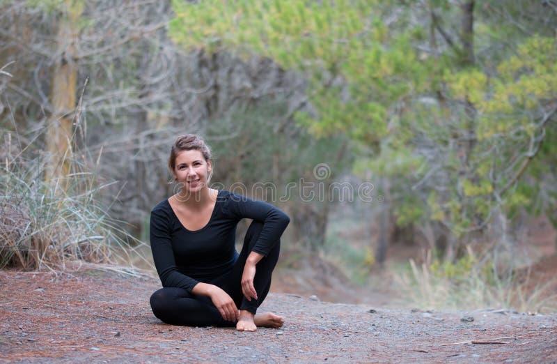 Το κορίτσι στη γυμναστική εξάρτηση κάθεται στο έδαφος σε ένα δάσος στοκ φωτογραφίες