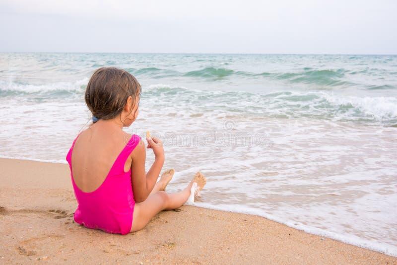 Το κορίτσι στη ρόδινη συνεδρίαση κοστουμιών λουσίματος στην παραλία, που τρώει μια γκοφρέτα και εξετάζει την απόσταση στοκ εικόνες