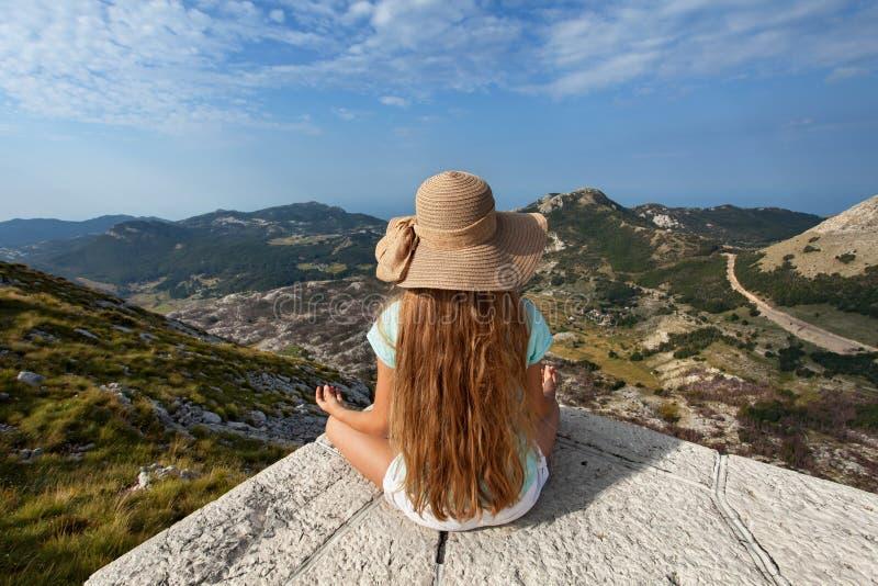 Το κορίτσι στη τοπ συνεδρίαση βουνών και θαυμάζει την άποψη στοκ φωτογραφίες