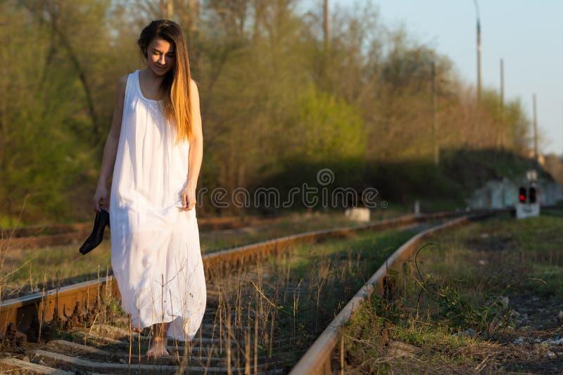 Το κορίτσι στο άσπρο φόρεμα χωρίς παπούτσια με τα παπούτσια διαθέσιμα πηγαίνει κατά μήκος του σιδηροδρόμου στοκ εικόνα με δικαίωμα ελεύθερης χρήσης