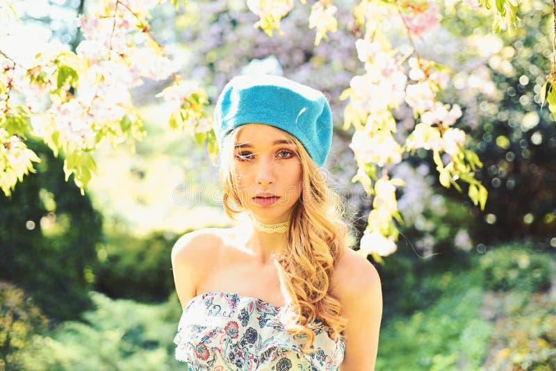 Το κορίτσι στο ήρεμο πρόσωπο, υποβάλλει προσφορά τα ξανθά κοντινά λουλούδια sakura, υπόβαθρο φύσης Γαλλική έννοια ύφους Η νέα γαλ στοκ εικόνα με δικαίωμα ελεύθερης χρήσης