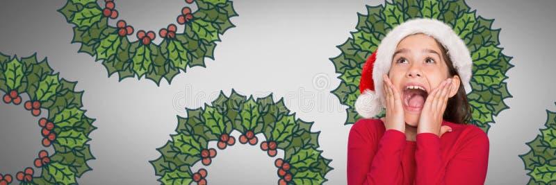 Το κορίτσι στο γκρίζο κλίμα με το καπέλο Santa κατέπληξε και εξέπληξε να φανεί επάνω και μεγάλοι κλώνοι ελαιόπρινου στοκ εικόνα