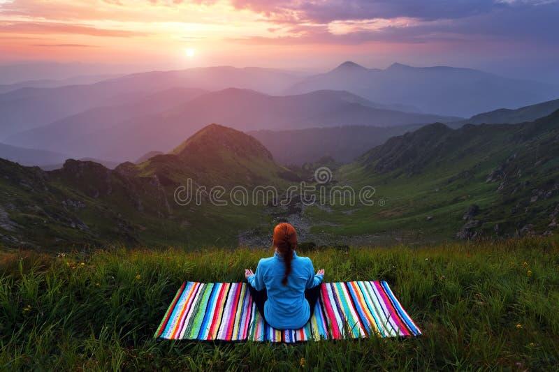 Το κορίτσι στο ζωηρόχρωμο χαλί ασκεί τη γιόγκα Όμορφη να γοητεύσει ανατολή, πορτοκαλής ουρανός με τα σύννεφα, υψηλά βουνά στην ομ στοκ εικόνα με δικαίωμα ελεύθερης χρήσης