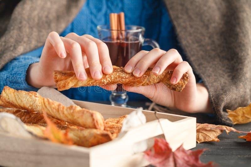 Το κορίτσι στο καρό τρώει το σκούπισμα cokies, καρυκεύοντας τα φύλλα πτώσης γύρω στοκ εικόνες με δικαίωμα ελεύθερης χρήσης