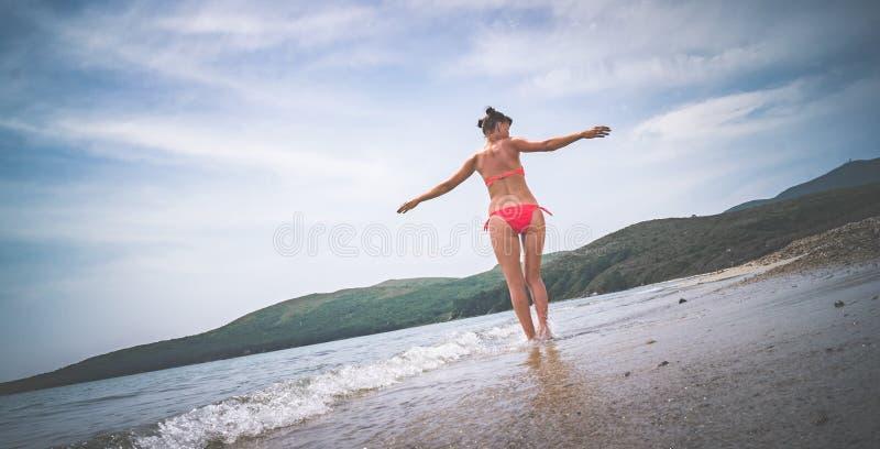 το κορίτσι στο κόκκινο κοστούμι λουσίματος που περιστρέφει στην παραλία στοκ φωτογραφία με δικαίωμα ελεύθερης χρήσης