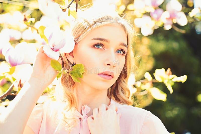 Το κορίτσι στο ονειροπόλο πρόσωπο, υποβάλλει προσφορά τα ξανθά κοντινά λουλούδια magnolia, υπόβαθρο φύσης Έννοια άνθισης άνοιξη α στοκ φωτογραφία με δικαίωμα ελεύθερης χρήσης