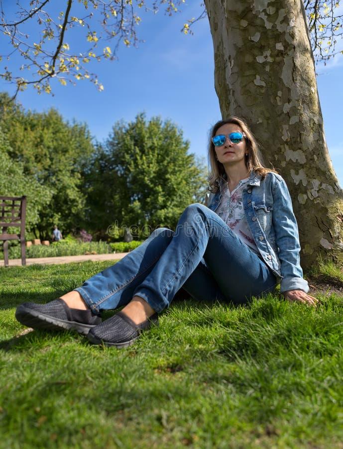 Το κορίτσι στο πάρκο κάθεται στο έδαφος από ένα δέντρο στοκ φωτογραφία με δικαίωμα ελεύθερης χρήσης