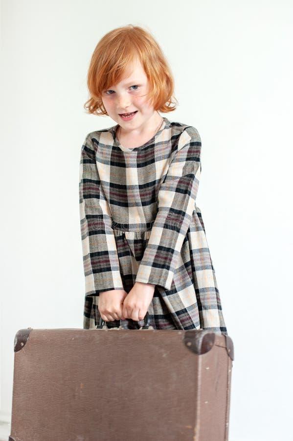 Το κορίτσι στο φόρεμα καρό κρατά μια βαλίτσα στοκ φωτογραφία με δικαίωμα ελεύθερης χρήσης