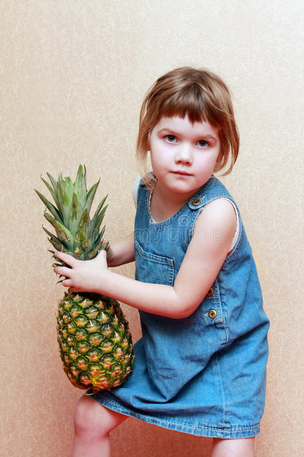 Το κορίτσι στο φόρεμα τζιν κρατά το μεγάλο πράσινο ανανά στοκ φωτογραφίες με δικαίωμα ελεύθερης χρήσης