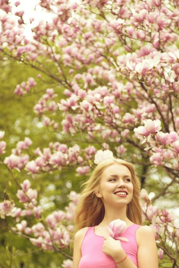Το κορίτσι στο όμορφο magnolia ανθίζει το ρόδινο δέντρο χρώματος στοκ φωτογραφίες