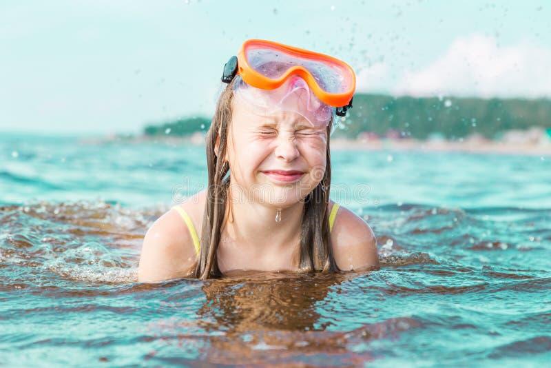 Το κορίτσι συμπίεσε τα μάτια της που έκλεισαν από τον ψεκασμό θάλασσας στοκ εικόνα