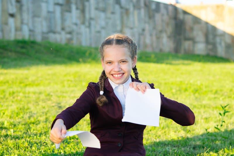 Το κορίτσι σχίζει στα χέρια ένα άσπρο φύλλο του εγγράφου σε ένα πάρκο στην οδό στοκ εικόνα