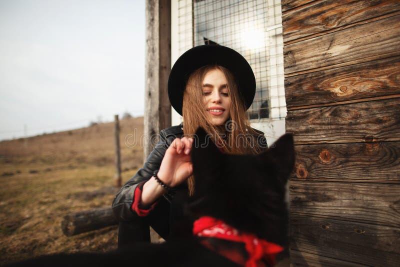 Το κορίτσι ταΐζει το μαύρο σκυλί της Brovko Vivchar στο fron του παλαιού ξύλινου σπιτιού στοκ εικόνα