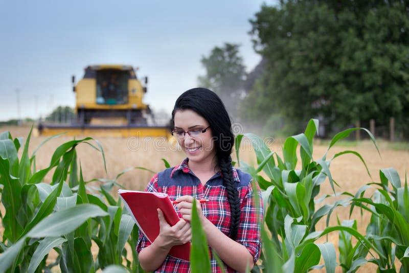 Το κορίτσι της Farmer στον τομέα με συνδυάζει τη θεριστική μηχανή στοκ φωτογραφία με δικαίωμα ελεύθερης χρήσης