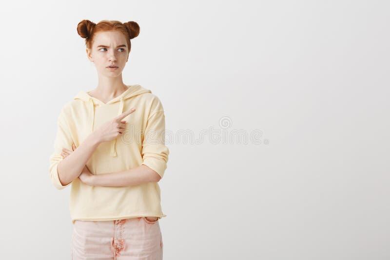 Το κορίτσι τονίζεται ότι η ένδειξη σε κάτι και η αποστροφή Ενοχλημένο ταραγμένο redhead θηλυκό με δύο χαριτωμένα κουλούρια στοκ φωτογραφίες