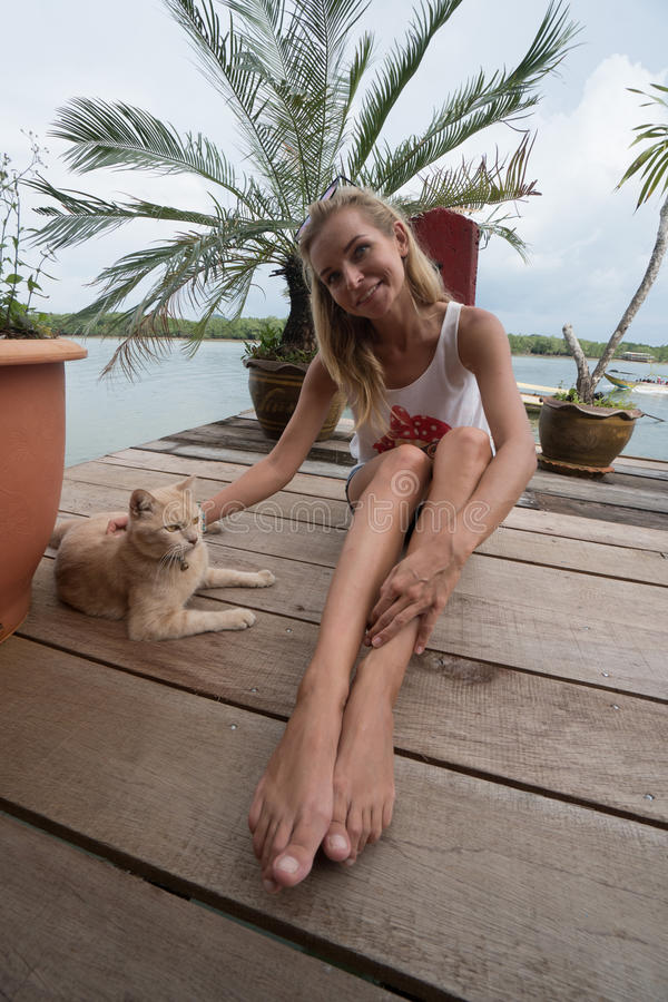 Το κορίτσι τουριστών αγκαλιάζει τη γάτα πιπεροριζών στην αποβάθρα Koh Panyee στοκ φωτογραφία με δικαίωμα ελεύθερης χρήσης