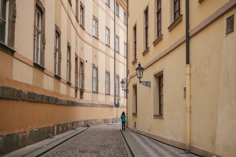 Το κορίτσι τουριστών στο πράσινο σακάκι περπατά κατά μήκος της όμορφης εγκαταλειμμένης στενής οδού στην Πράγα μεταξύ δύο ιστορικώ στοκ εικόνες με δικαίωμα ελεύθερης χρήσης