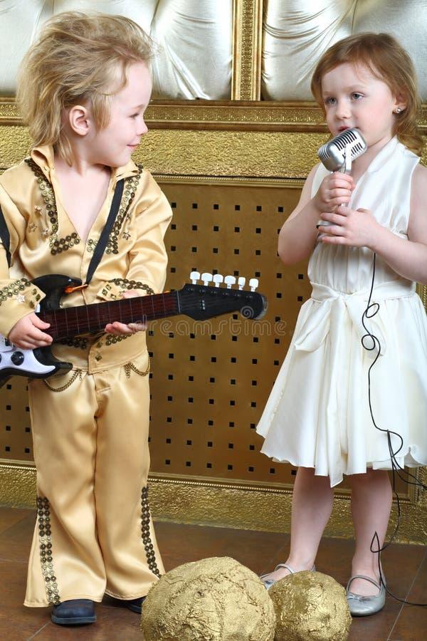 Το κορίτσι τραγουδά ένα τραγούδι και ο λαϊκός μουσικός παίζει την κιθάρα στοκ εικόνα