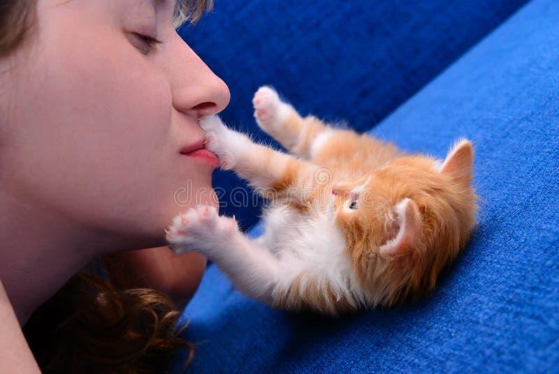 Το κορίτσι φιλά ένα κόκκινο γατάκι στοκ φωτογραφία