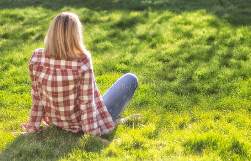 Το κορίτσι χαλαρώνει στο λιβάδι Η ξανθή όμορφη νέα γυναίκα κάθεται στη χλόη και απολαμβάνει τον ήλιο Υπαίθριος r Φθορά στοκ φωτογραφίες
