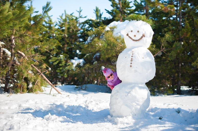 Το κορίτσι το χειμώνα που κρύβει πίσω από έναν μεγάλο χιονάνθρωπο Παιδιά στα ρόδινα σακάκια και γυαλιά που πηδούν στον ήλιο στοκ εικόνα με δικαίωμα ελεύθερης χρήσης