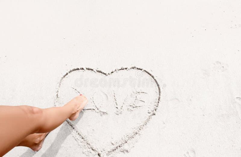 Το κορίτσι χρωματίζει την καρδιά στην άμμο στοκ εικόνες με δικαίωμα ελεύθερης χρήσης