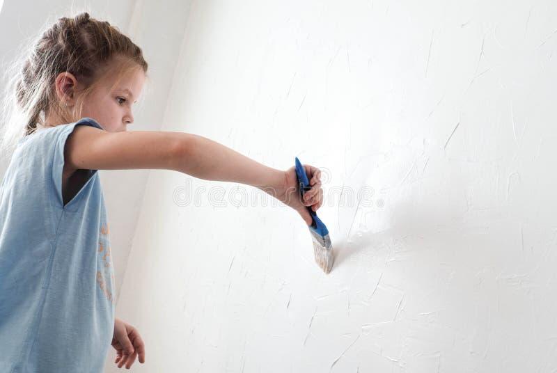 Το κορίτσι χρωματίζει τον τοίχο του δωματίου με μια βούρτσα στοκ εικόνα