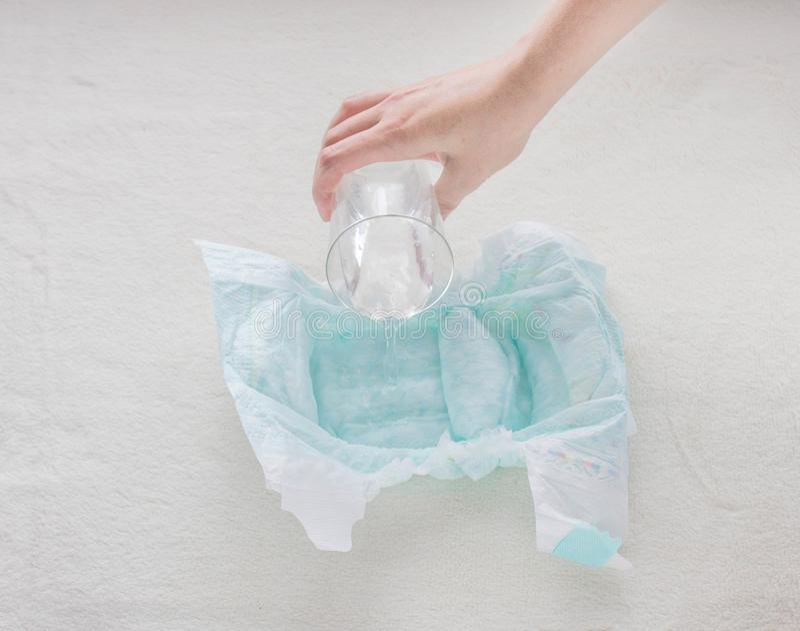 Το κορίτσι χύνει ένα ποτήρι του νερού σε μια πάνα μωρών, κινηματογράφηση σε πρώτο πλάνο στοκ εικόνες