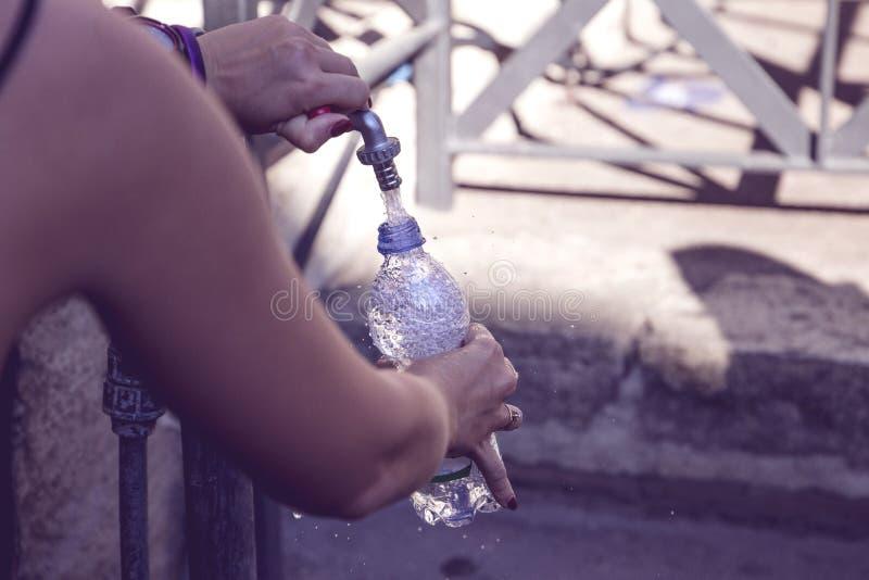 Το κορίτσι χύνει το νερό σε ένα μπουκάλι από την πηγή οδών στοκ φωτογραφίες