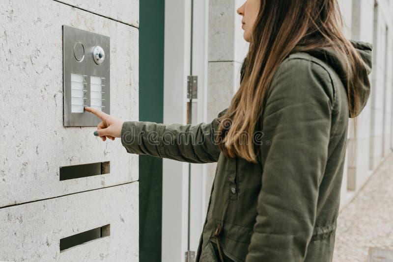 Το κορίτσι ωθεί το κουμπί doorphone ή καλεί την ενδοσυνεννόηση στοκ φωτογραφία με δικαίωμα ελεύθερης χρήσης