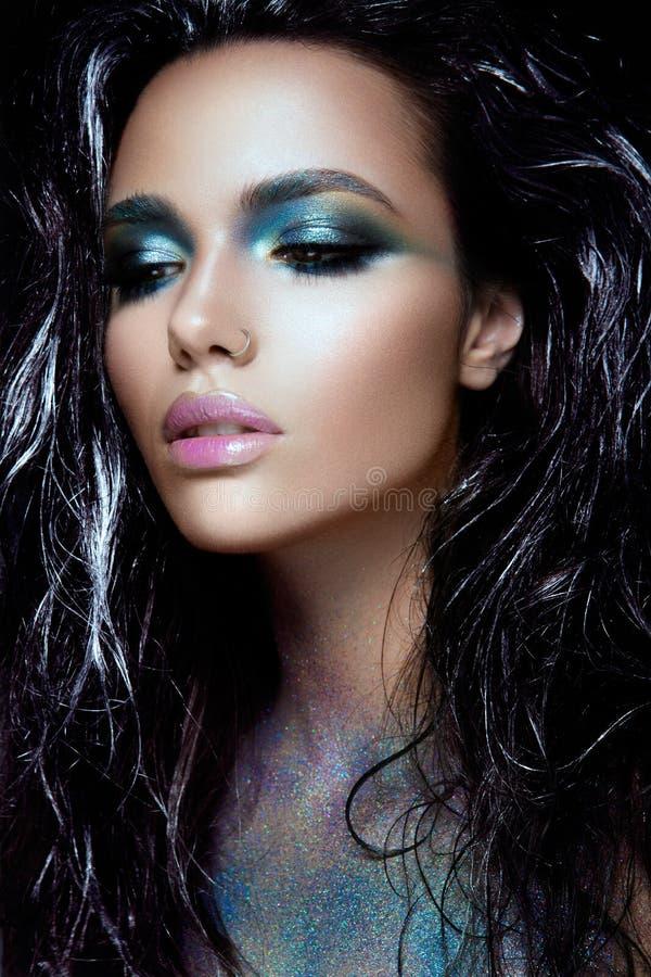 Το κορίτσι Beautyful με το μπλε ακτινοβολεί στο πρόσωπό της στοκ εικόνες