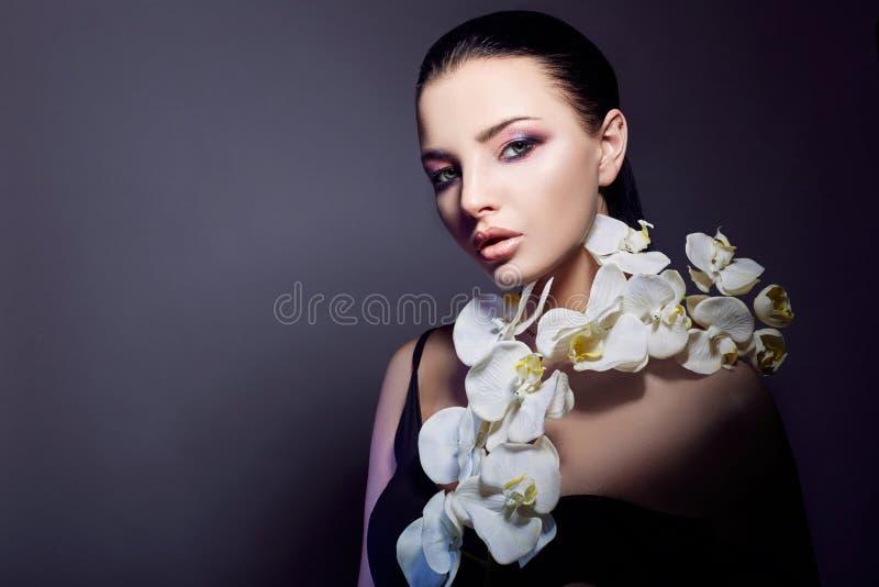 Το κορίτσι Brunette με τη ορχιδέα ανθίζει στο πρόσωπο και το στήθος, το πορτρέτο ομορφιάς ενός τέλειου makeup, τα όμορφα μάτια κα στοκ φωτογραφία