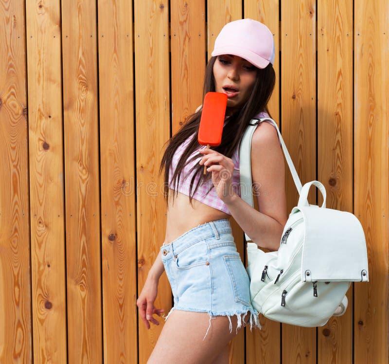 Το κορίτσι Hipster που φορά τη ρόδινα κορυφή, τα τζιν και το καπέλο του μπέιζμπολ με την άσπρη τοποθέτηση σακιδίων πλάτης ενάντια στοκ εικόνες