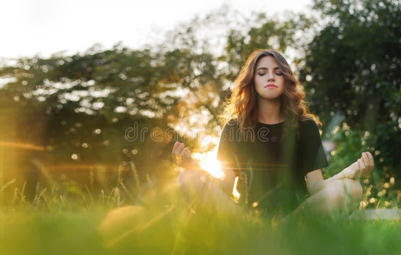 Το κορίτσι meditates στη χλόη στο ηλιοβασίλεμα στοκ εικόνες