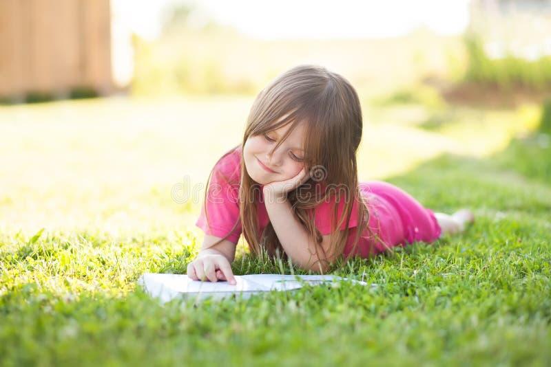 Το κορίτσι Preschooler μαθαίνει να διαβάζει υπαίθρια στοκ φωτογραφία