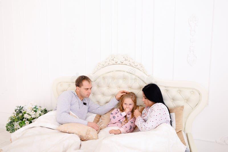 Το κορίτσι RKid άρρωστο, παίρνει την κρύα μητέρα σκουπίζει snot στο κρεβάτι στοκ εικόνα