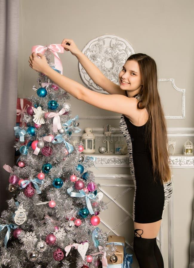 Το κορίτσι Teenag διακοσμεί το χριστουγεννιάτικο δέντρο με τα παιχνίδια Χριστουγέννων στοκ εικόνες