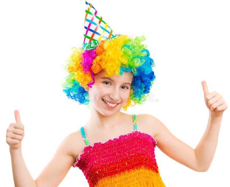 Το κορίτσι Yappy στην περούκα κλόουν παρουσιάζει αντίχειρες που απομονώνονται επάνω στοκ φωτογραφία