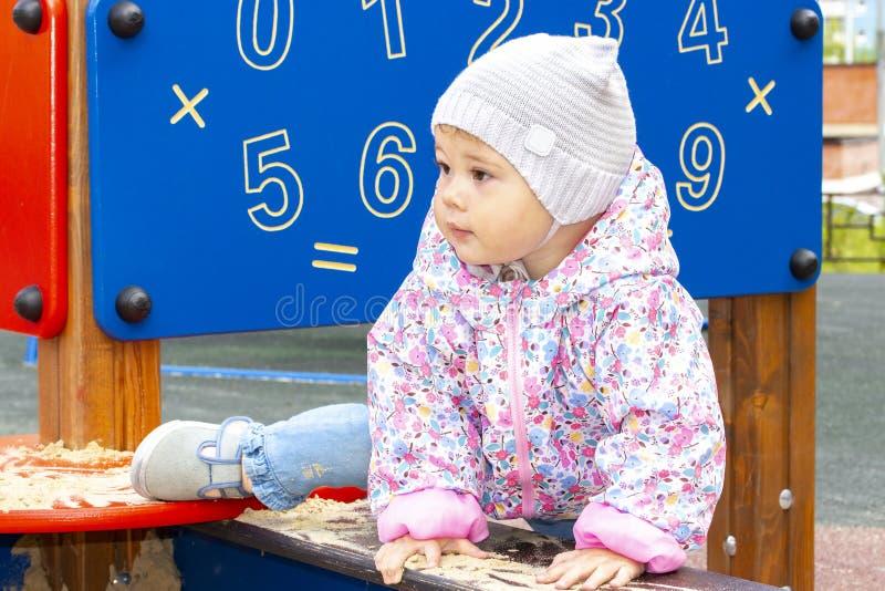 Το κοριτσάκι σε ένα σακάκι και ένα καπέλο αναρριχείται στο Sandbox, ρίχνει το πόδι της πέρα από την πλευρά του Sandbox Κορίτσι σε στοκ εικόνες με δικαίωμα ελεύθερης χρήσης